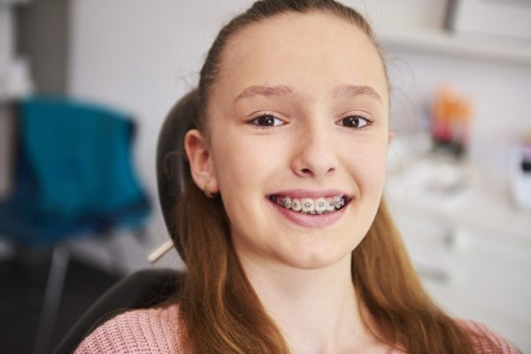 Portrait of smiling child with braces in dentist's office