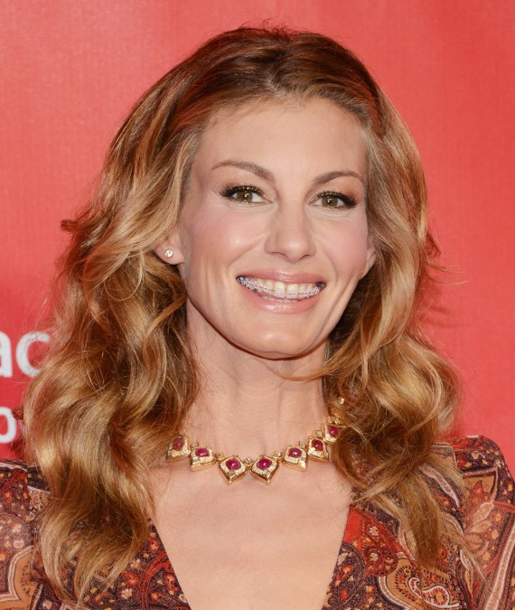 A portrait of Faith Hill wearing clear braces and an ornate red and gold necklace.